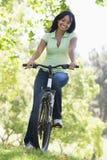 自行车微笑的妇女 免版税库存照片