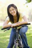 自行车微笑的妇女 免版税库存图片