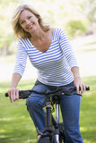自行车户外微笑的妇女 图库摄影