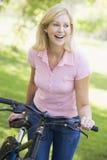 自行车户外微笑的妇女 库存图片