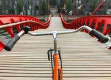 自行车把手POV视图 在木红色Python桥梁的橙色自行车在阿姆斯特丹,荷兰 免版税库存图片
