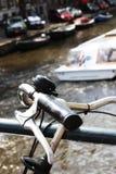 自行车把柄特写镜头有通过游览的小船的后边 免版税库存图片