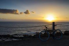自行车日落峭壁海洋 免版税图库摄影