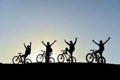 自行车的人们在日落 免版税库存图片