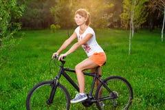 自行车的女孩在领域 免版税库存照片