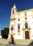 自行车的妇女在卡尔穆教会Igreja前面在南葡萄牙,欧洲做缓慢的卡尔穆做卡尔穆,法鲁,阿尔加威地区 库存图片