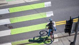 自行车的妇女穿过路在行人交叉路 免版税库存图片