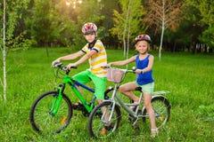 自行车的孩子在草的领域 免版税图库摄影