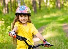自行车的小女孩在看照相机和微笑的森林里 免版税库存照片