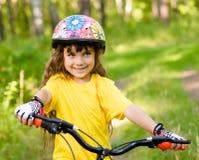 自行车的小女孩在看照相机和微笑的森林里 库存图片