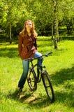 自行车的少妇在春天森林 免版税库存图片