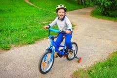 自行车的情感愉快的孩子在绿色公园是愉快的并且从乐趣尖叫 免版税库存照片