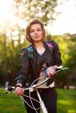 自行车的梦想的少妇在日落的绿色公园 库存图片