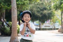 头戴自行车盔甲的愉快的孩子户外 免版税库存图片