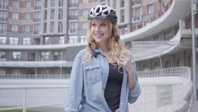 自行车盔甲身分的俏丽的白肤金发的妇女与以都市建筑学为背景的自行车 夫人继续下去  股票录像