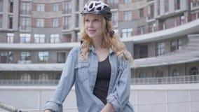 自行车盔甲身分的画象俏丽的白肤金发的妇女与以都市建筑学为背景的自行车 ?? 股票录像