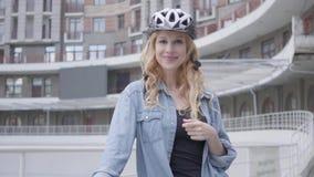 自行车盔甲身分的画象逗人喜爱的白肤金发的妇女与以都市建筑学为背景的自行车 夫人是 股票录像