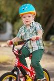 自行车盔甲骑马的孩子 库存照片