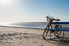 自行车站立在海滩的近的长凳 库存照片