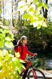 自行车结构的女孩骑自行车者在公园每明亮的晴天 免版税库存图片
