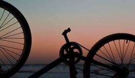 自行车车轮和脚蹬在日落 免版税库存照片