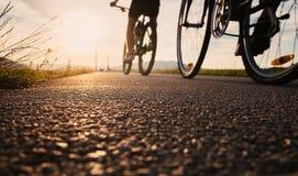 自行车轮子关闭在沥青日落路的图象 库存图片