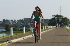 自行车骑马的女孩 免版税库存图片