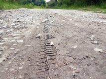 自行车,拖拉机,挖掘机,汽车,在泥泞的足迹的汽车轮胎轨道 泥和轮子在路追踪在雨以后 库存照片