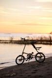 自行车Strida剪影在日落的在海滩 免版税库存图片