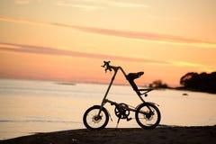 自行车Strida剪影在日落的在海滩 免版税图库摄影