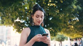 自转观点的站立在城市公园和使用她的电话的黑成套装备的可爱的少妇,看  股票录像
