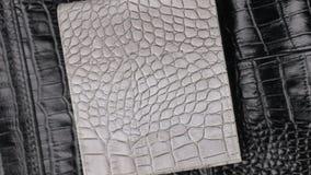 自转,两在黑皮肤构造鳄鱼皮肤,灰色皮革钱包说谎 特写镜头 影视素材