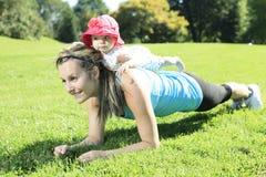 舒展与婴孩肌肉的母亲训练 免版税库存照片