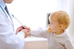 舒展为听诊器的感兴趣婴孩 图库摄影