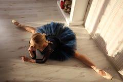 舒展做准备在家庭内部,在地板上的分裂的美丽的少妇芭蕾舞女演员 免版税库存图片