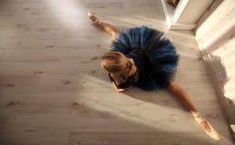 舒展做准备在家庭内部,在木地板上的分裂的美丽的少妇芭蕾舞女演员 免版税库存照片