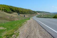 舒展入距离的一条绞的高速公路反对一个美好的春天风景,领域,草甸,森林的背景和 免版税库存照片