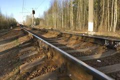 舒展入距离的被日光照射了弯曲的铁路轨道的看法 库存图片