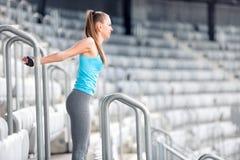 舒展和做体操的健身女孩在体育场台阶行使 制定出概念的运动员女孩和人 免版税库存图片