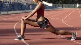 舒展和给她的腿加热的两种人种的夫人在开始前跑干涉 库存图片