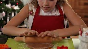 舒展圣诞节曲奇饼面团的圣诞老人帽子的女孩 影视素材