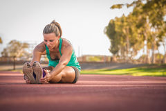 舒展在一条连续轨道的女运动员 图库摄影