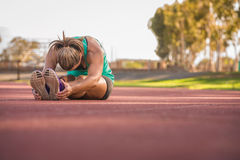 舒展在一条连续轨道的女运动员 免版税库存图片