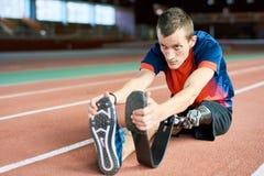 舒展在体育场内的有残障的运动员 免版税库存图片