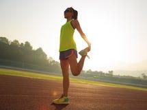 舒展在体育场轨道的妇女赛跑者腿 库存照片