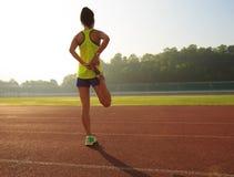 舒展在体育场轨道的妇女赛跑者腿 库存图片