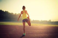 舒展在体育场轨道的妇女赛跑者腿 免版税库存照片