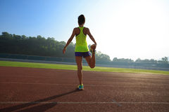 舒展在体育场轨道的妇女赛跑者腿 免版税库存图片