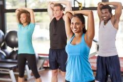 舒展在健身房的不同种族的小组 免版税库存图片