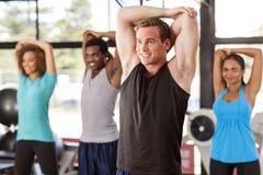 舒展在健身房的不同种族的小组 免版税图库摄影